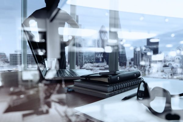 double exposure of business documents on office table with smart phone and digital tablet and london city blurred view and man thinking in the background